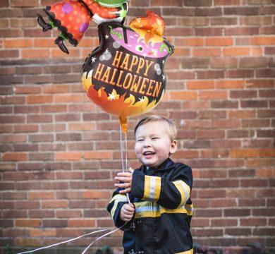 bambino costume pompiere e palloncini halloween
