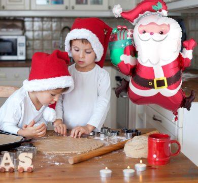 due bambini con cappello di babbo natale cucinano biscotti