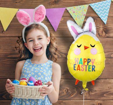 bambina con uova di pasqua colorate e palloncino buona pasqua