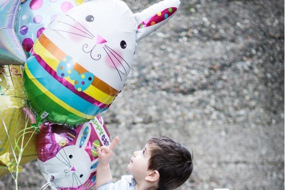 bambino guarda palloncini conigli buona pasqua