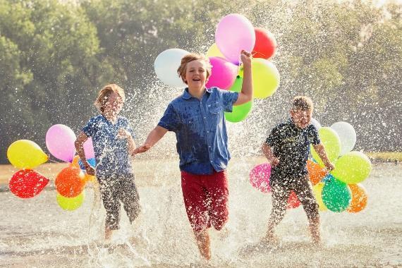 bambini giocano nell'acqua con palloncini colorati